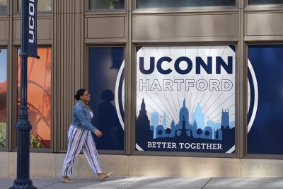 A student walks outside of the Hartford Times Building pas a sign that reads UConn Hartford: Better Together.
