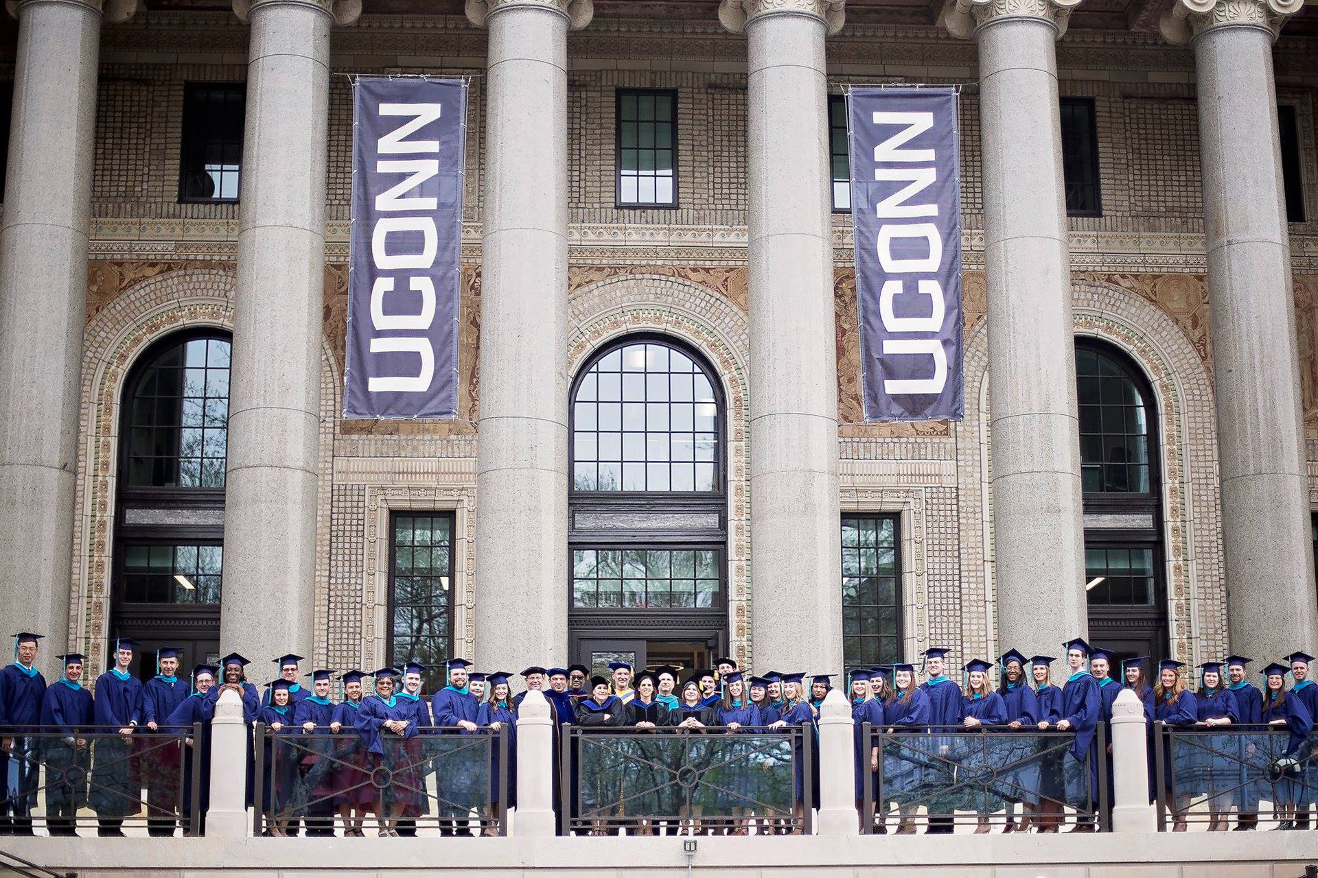 A large group of alumni and faculty in academic regalia lined up in front of the Hartford Times Building beneath two large UConn banners.