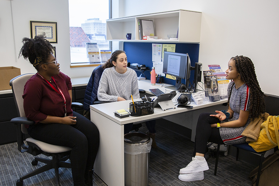 Three graduate students have a discussion in the public policy main office.