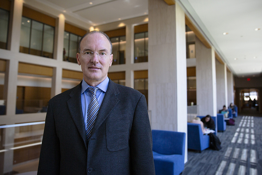 Thomas Craemer, a professor in the Department of Public Policy, poses in the hallway of the UConn Hartford campus.