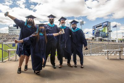 At front Alexandra DeGirolarno '21 MPA, back row from left Ciara Hanlon '21 MPA, Michael Lucas '21 MPA, Kevin Fitzgerald '21 MPA, and Devon Aldave '21 MPA at the 2021 Masters/ 6th year certificate Commencement ceremony at Pratt & Whitney, Rentshler Field on May 12, 2021.